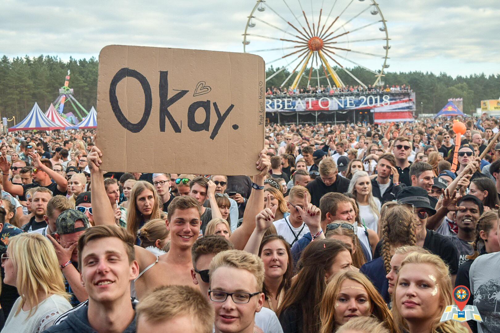 """Vor der Mainstage hält ein junger Mann ein Schild mit der Aufschrift """"Okay"""" in die Höhe. (Bild: Chelsy Haß)"""