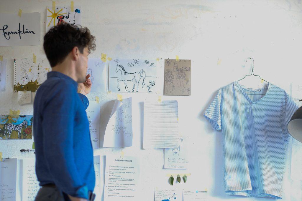 """Fynn steht vor seinem """"Vision Board"""" für die bevorstehende Ausstellung. (Bild: Christian J. Ahlers)"""